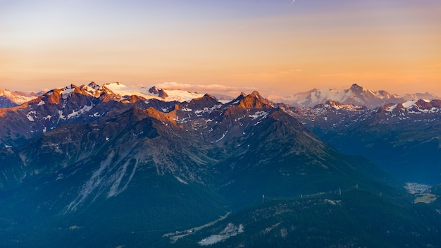Last soft sunlight over rocky mountain peaks, ridges and valleys of the alps at sunrise.