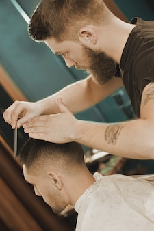 Last styling steps. vertical shot of a bearded barber styling his client in a barbershop