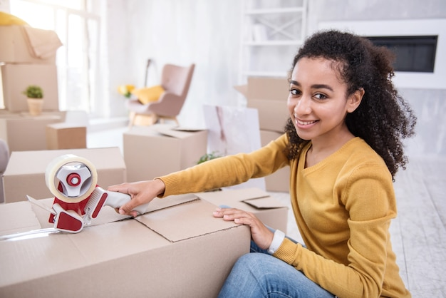 Last touches. beautiful curly-haired girl posing for the camera and smiling while sealing a box with belongings with adhesive tape