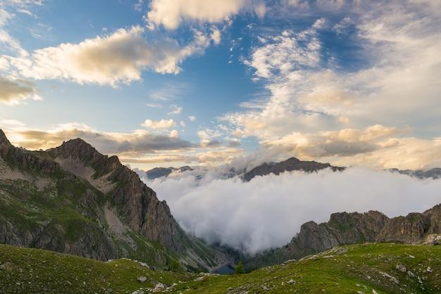 Последний теплый солнечный свет в альпийской долине со светящимися горными вершинами и живописными облаками.