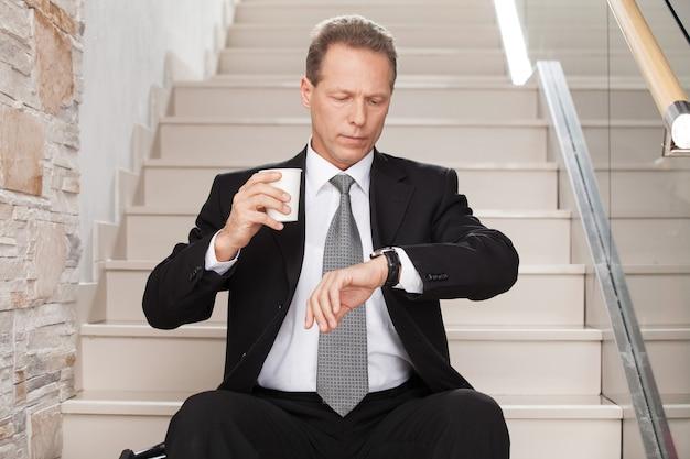 또 늦다. 걱정된 성숙한 남자는 정장을 입고 커피 컵을 들고 계단에 앉아 시간을 확인합니다.