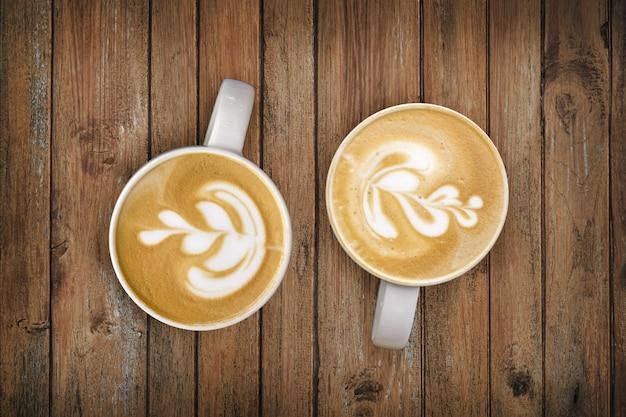 Late art on coffee cup on wood