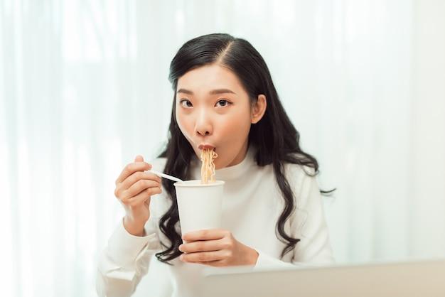 늦은 저녁. 인스턴트 국수 컵을 먹는 소녀는 큰 식욕으로 구입합니다.