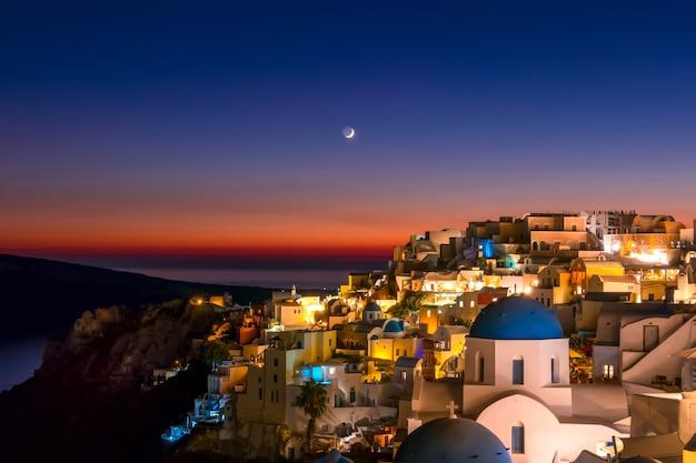티라 섬의 이아 (oia) 지붕 위의 늦은 저녁과 달