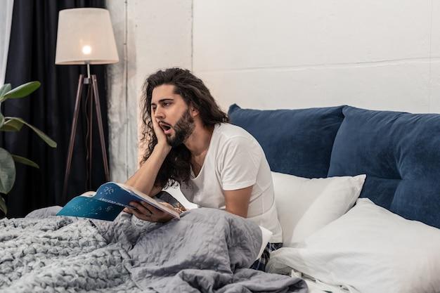 夜遅く。寝ることを考えながら本を手に座っている素敵なハンサムな男