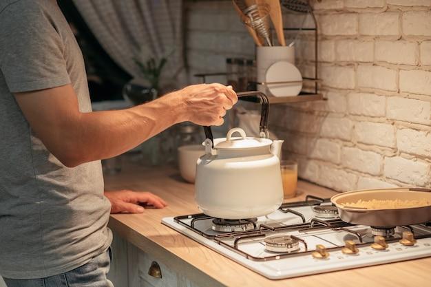 Привычка к позднему чаю. обрезанный снимок человека, ставящего старый чайник на плиту. современная кухонная стена.