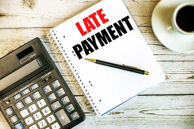Поздняя оплата написана на белой бумаге возле кофе и калькулятора на светлом деревянном столе. бизнес-концепция