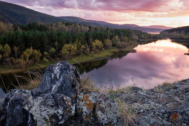 배경에 강 숲이 있는 늦은 여름 풍경 아름다운 반사와 fo의 바위