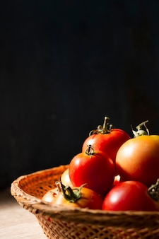 Lateral view basket full with tomatoes
