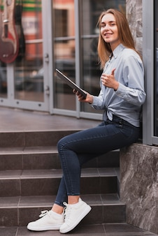 Lateral view blonde girl holding a tablet