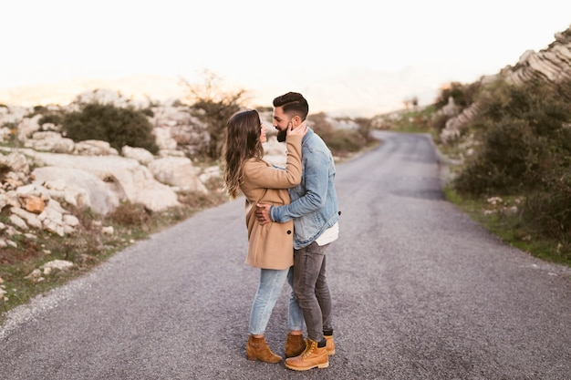 Lateral view couple embracing on road