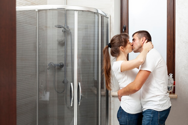 Lateral view couple kissing in bathroom