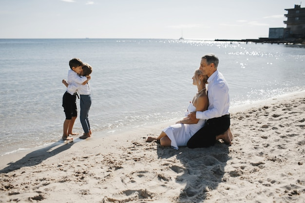 Lateral view of couple which is sitting on the sandy beach near the sea and looking on the two little sons who are hugging