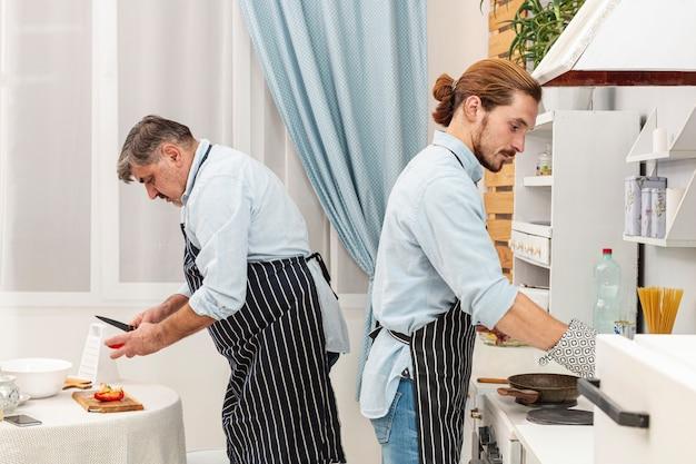 Боковой вид отец и сын готовят