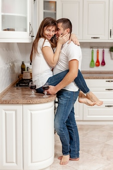Lateral view man embracing his girlfriend in kitchen