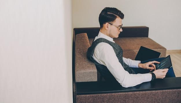 Боковой вид уверенного в себе кавказского фрилансера в очках, работающего над планшетом, сидя на диване
