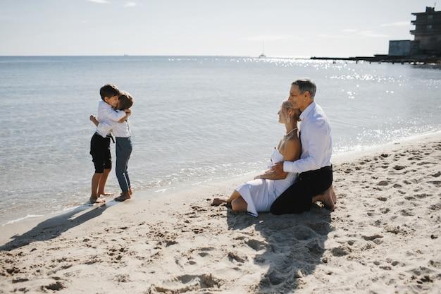 Боковой вид пара, которая сидит на песчаном пляже у моря и смотрит на двух маленьких сыновей, которые обнимаются