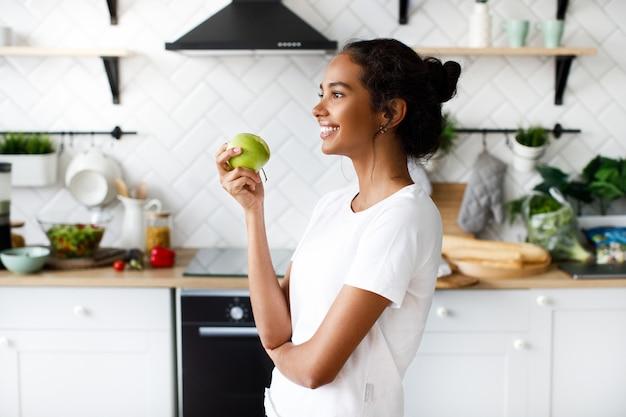 Боковой вид улыбающейся привлекательной женщины-мулата, которая держит яблоко и смотрит далеко на белую современную кухню