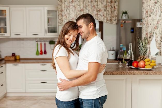 Боковой вид улыбается пара, охватывающей на кухне