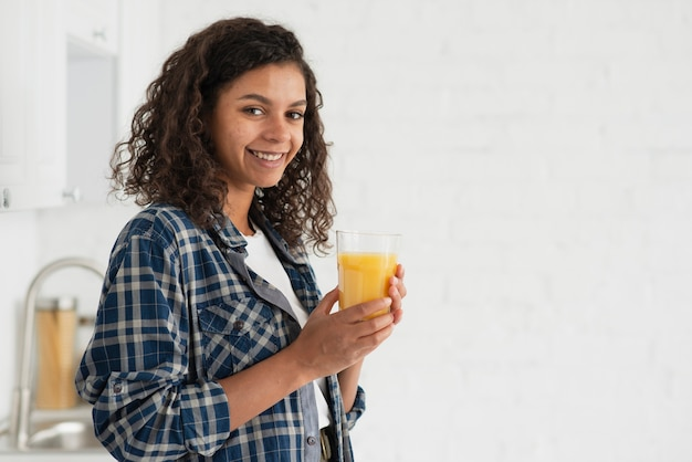 Lateral view smiling woman drinking orange juice