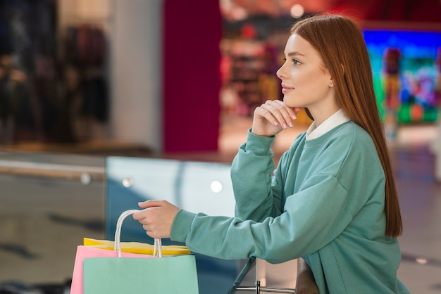 Lateral view thinking woman holding shopping bags