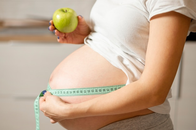 Lateral view woman hands holding an apple and measuring her belly