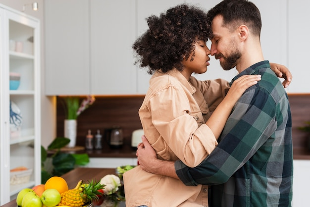 Lateral view young couple embracing in kitchen