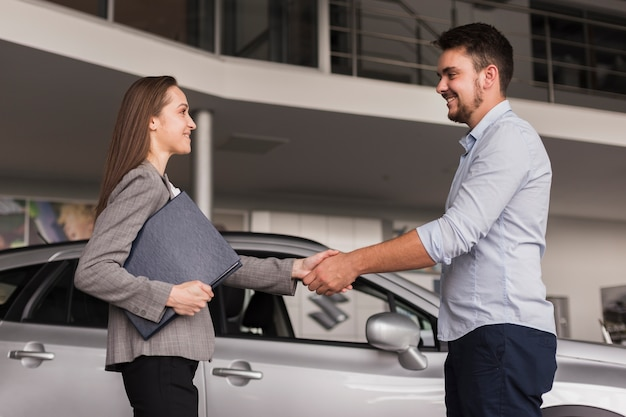 Lateral view young man shaking hands with car dealer