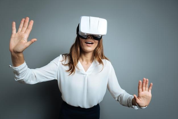 最新のイノベーション。 3dメガネをかけて、灰色の背景に立っている間、仮想現実にいるポジティブな若い喜びの女性
