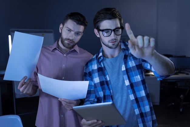 최신 기술 개발. 가상 현실을 테스트하는 동안 태블릿을 들고 감각 화면을 누르고 좋은 잘 생긴 지능형 남자