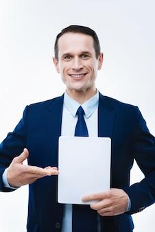 最新の技術。タブレットを指して、仕事に使用しながら笑顔で幸せな素敵な喜んでいるビジネスマン