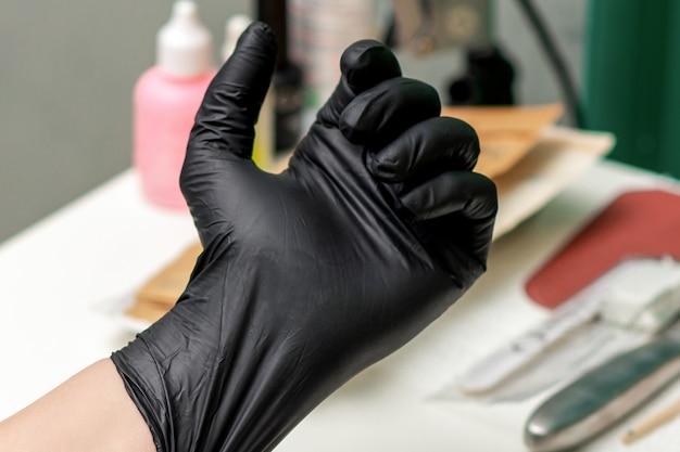 화장품이나 의료 절차 전에 손에 있는 라텍스 검은 장갑을 닫습니다.