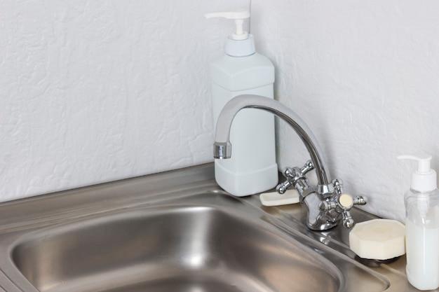 라텍스 장갑, 금속 싱크대 세척 디스펜서의 액체 비누. 위생 용품