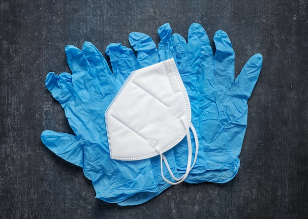 Latex medical gloves and white protective mask