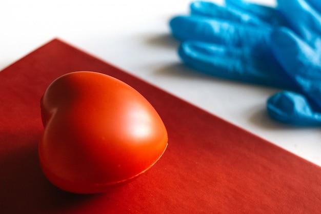 Латексная защитная резиновая перчатка с красным сердцем рядом. концепция здравоохранения медицины. коронавирусная защита ковид-2019. медицинская концепция. медицинское образование.