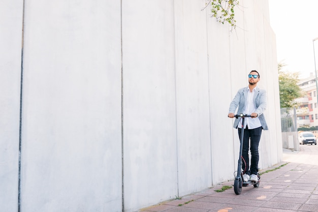 Latin adult man with sunglasses, well dressed and drive electric scooter on the street with a white blind background