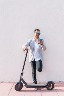 Latin adult man with sunglasses, well dressed and electric scooter talking on his mobile phone sitting on the street with a white wall background