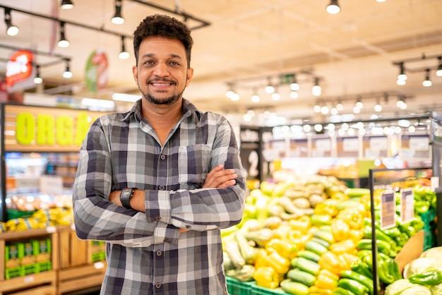 Латинская америка в супермаркете. улыбающийся человек со скрещенными руками и глядя в камеру