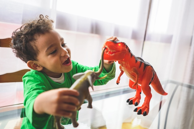 Latin american boy playing with animal toys at home.