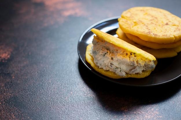 Латиноамериканский завтрак арепас (арепа) из кукурузного теста с сыром и зеленью. кухня венесуэлы и колумбии. крупным планом, темный фон, копия пространства