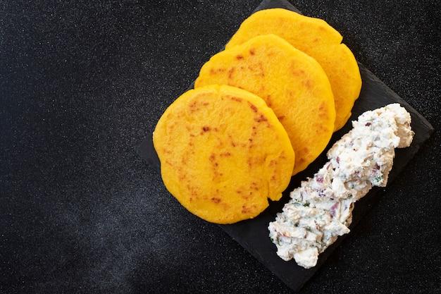 Латиноамериканский завтрак арепас (арепа) из кукурузного теста с сыром и зеленью подается на черной тарелке. кухня венесуэлы и колумбии. вид сверху, черный фон, копия пространства