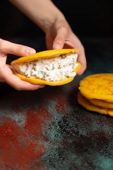 Латиноамериканский завтрак арепас (арепа) из кукурузного теста с сыром и зеленью. женские руки держат арепа. кухня венесуэлы и колумбии. взгляд крупного плана, темная предпосылка, космос экземпляра. вертикальный