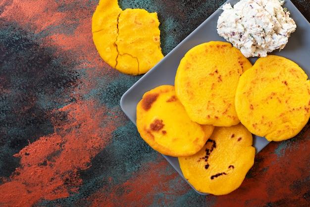 Латиноамериканский завтрак арепас из кукурузного теста с сыром и зеленью. кухня венесуэлы и колумбии. вид сверху, яркий фон, копия пространства