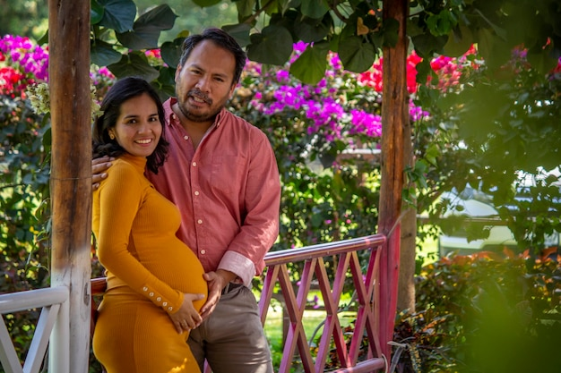 Latin american couple waiting for a baby in a beautiful park full of flowers