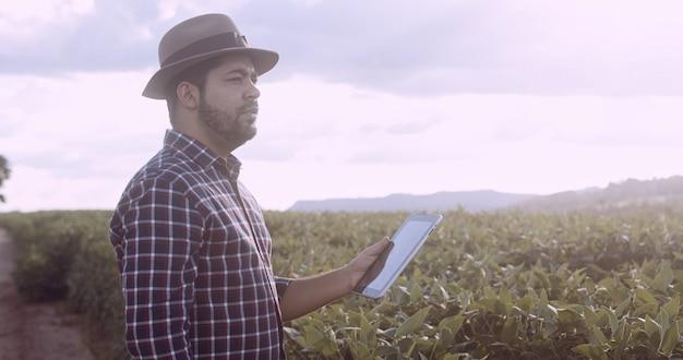 タブレットで作物の開発を調べ、大豆農園に取り組んでいるラテンアメリカの農家。