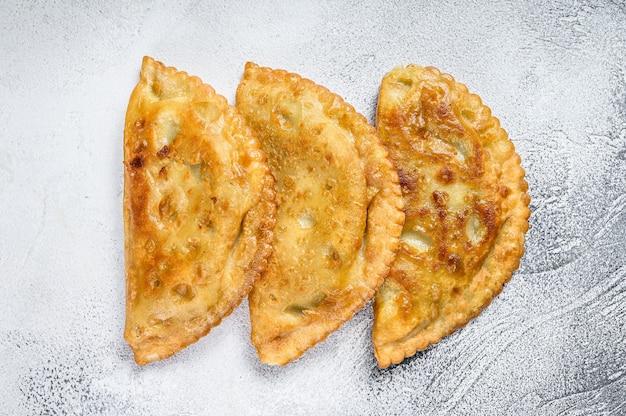 Латиноамериканские жареные эмпанада пикантные пирожные с мясом. белый фон. вид сверху.