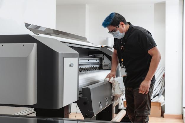 대형 포맷 플로터를 청소하는 마스크를 쓴 라틴 아메리카 남자. 개념 비즈니스와 코로나 바이러스.