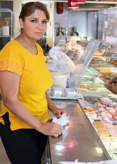라틴 아메리카 성숙한 여성은 패스트 푸드점에서 일합니다.