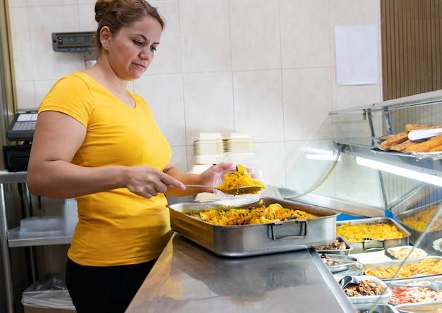 Латиноамериканская зрелая женщина работает в магазине быстрого питания