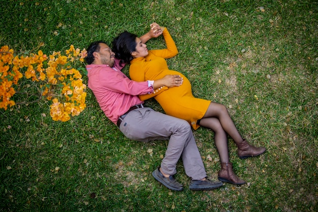 Latin american pregnant couple laying down in a yellos flowers field